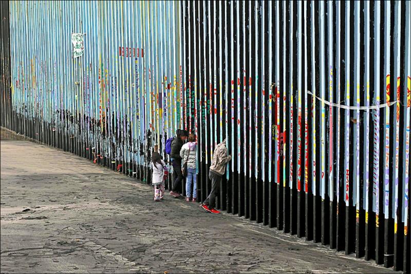 在墨西哥下加利福尼亞州,移民透過邊境柵欄探看美國境內。(法新社檔案照)