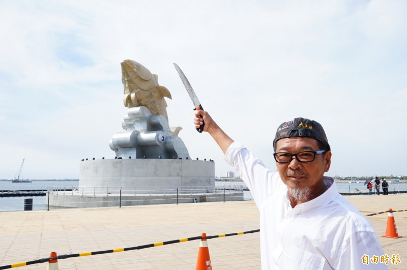 民俗專家廖大乙拿著鈍鋸對著台灣燈會主燈「巨鮪來富」,象徵著「鋸尾。(記者陳彥廷攝)