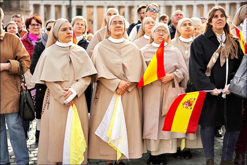 一群修女在教宗方濟各於俯瞰梵蒂岡聖伯多祿廣場的窗台旁誦念三鐘經午禱文時,專注仰望。方濟各公開承認修女不時成為神職人員的性侵受害者。(美聯社檔案照)