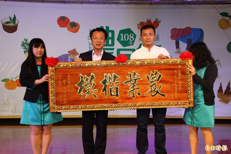 王國輝(右)研究花生有機栽培加工,獲選為全國模範農民,由嘉義縣長翁章梁(左)表揚。(記者林宜樟攝)