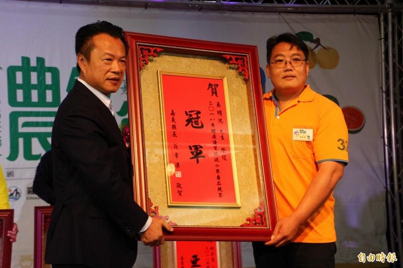 嘉義縣長翁章梁(左)表揚小果番茄冠軍吳明鴻(右)。(記者林宜樟攝)