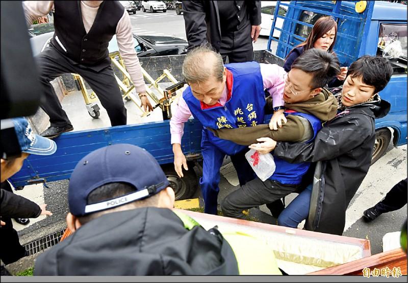 統促黨總裁張安樂昨率眾抬棺至立法院抗議,張安樂不慎從載送棺材的貨車上跌落,差點摔進棺材裡,旁人見狀趕緊上前攙扶。(記者羅沛德攝)