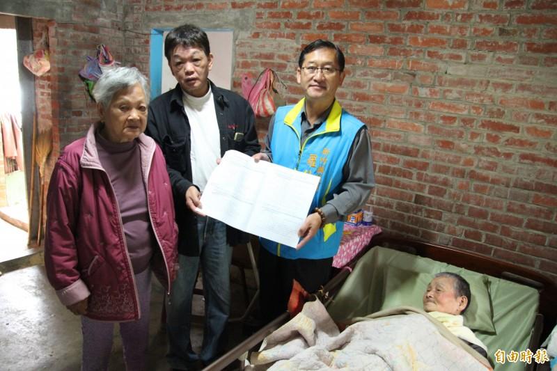 新竹縣議員羅仕琦(立者右)拿著臥床近5個月的阿公劉阿昌的身障鑑定表,抨擊醫院醫師根本就是「拿雞毛當令箭」,或許合法,但卻完全不近人情。(記者黃美珠攝)