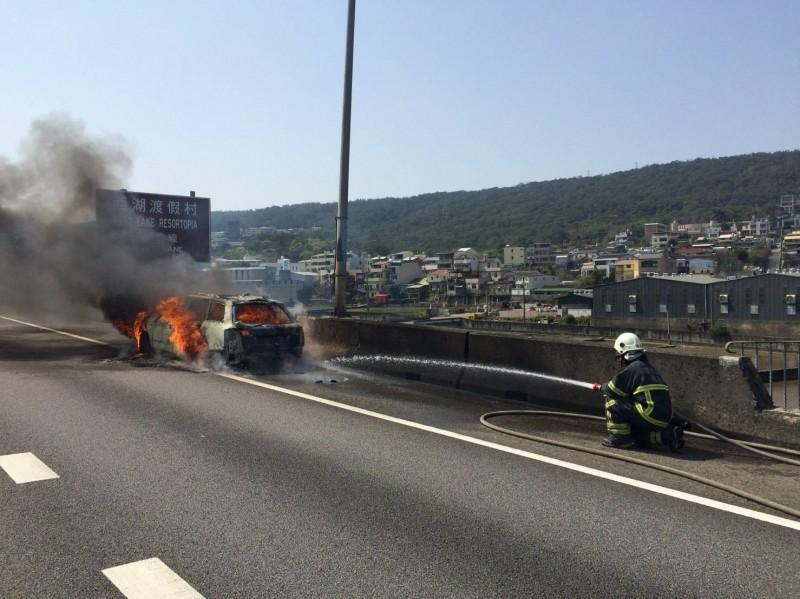 小客車被大火吞噬,消防隊員噴水灌救。(記者彭健禮翻攝)