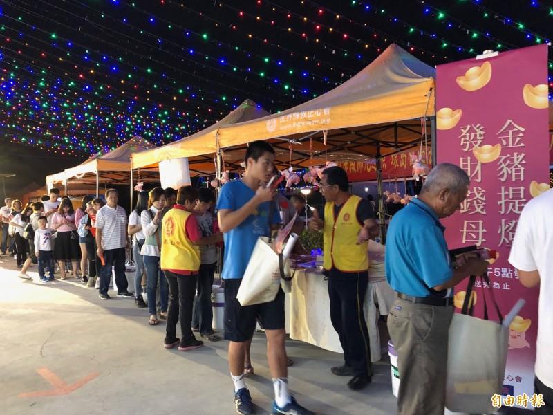 世界佛教正心會的「行動佛殿車」進駐台灣燈會,每天限量發放美金1元現鈔發財金,引來人潮。(記者陳彥廷攝)