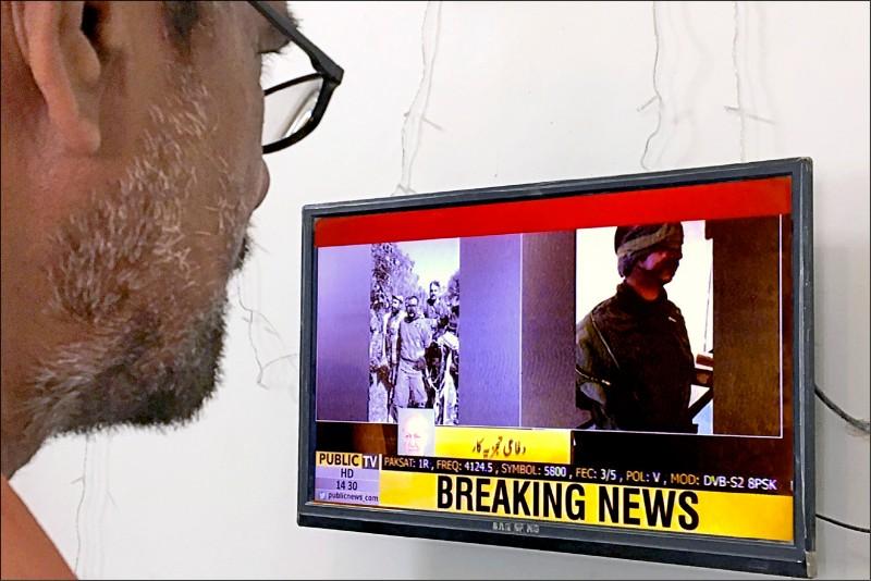 一名印度男子二月廿七日看著印度空軍飛官瓦塔曼遭巴基斯坦擊落並被俘虜的電視新聞快報。(路透)