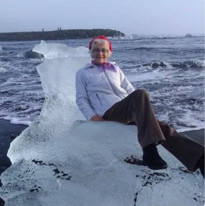 美國德州阿嬤斯特朗(Judith Streng)到冰島旅行時,坐上岸邊的「冰山王座」。(圖擷自@Xiushook推特)