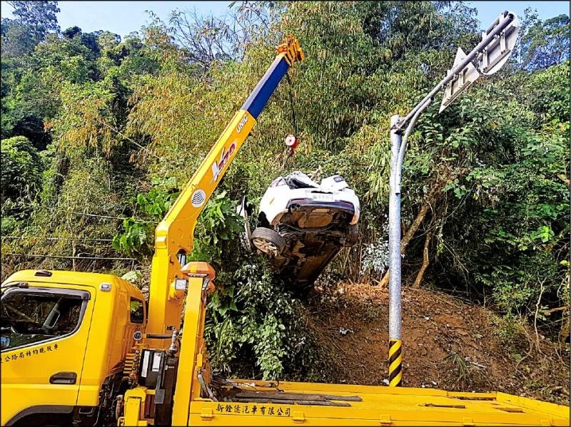 自小客車衝上山邊斜坡,動用吊車才順利將車子吊離現場。(記者王秀亭翻攝)