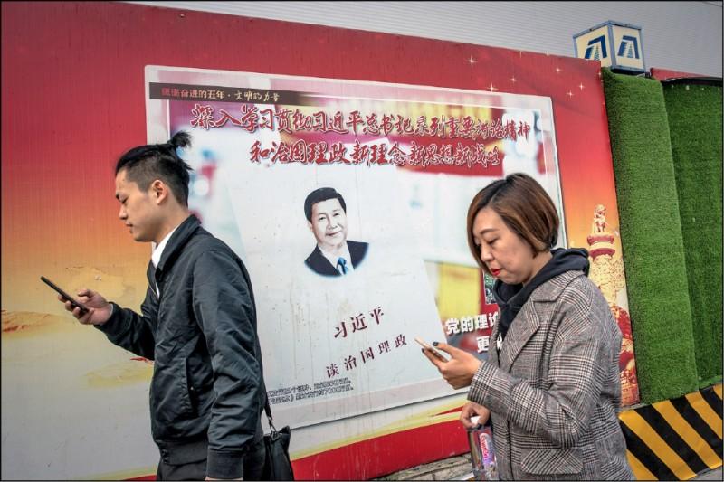 北京市民二日在兩會舉行前夕,行經表彰中國國家主席習近平的宣傳海報。(歐新社)