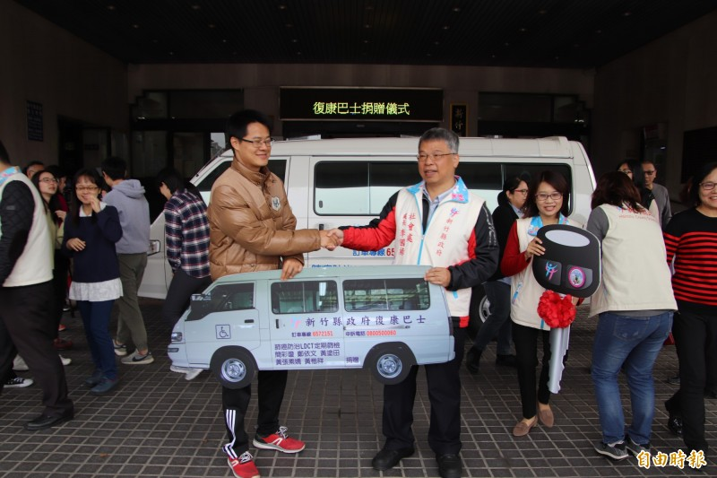 黃先生(左)跟太太把對偶像、父母的個人小愛化成對社會的大愛,今天捐贈復康巴士給新竹縣政府,由社會處處長李國祿(右)代表收下。(記者黃美珠攝)