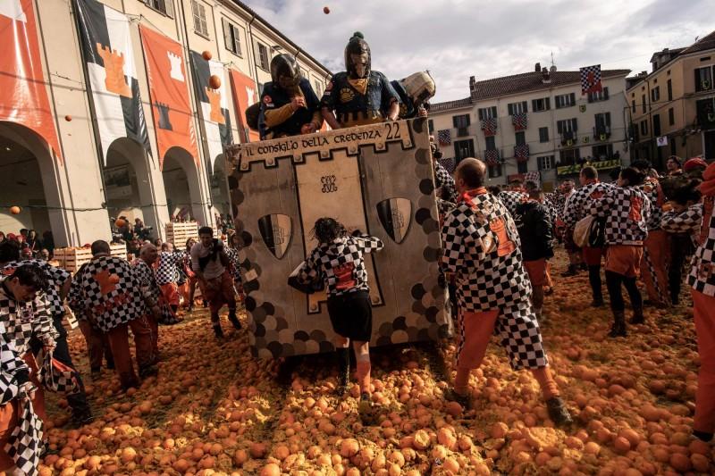 義大利北部小鎮伊夫雷亞每年春天都會舉行「橘子戰爭」,畫面中經過裝扮的人群腳下踩的、車輛輾過的都是新鮮的橘子。(法新社)