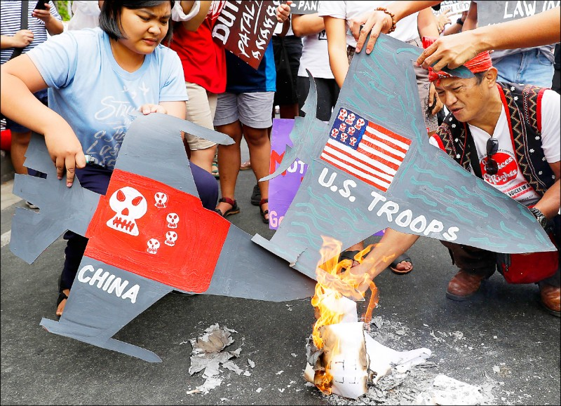 菲律賓示威者五日在首都馬尼拉的美國大使館外焚燒美國與中國戰機模型,對菲國可能在《美菲共同防禦條約》下,被捲入美中軍事衝突表達憂心。(美聯社)