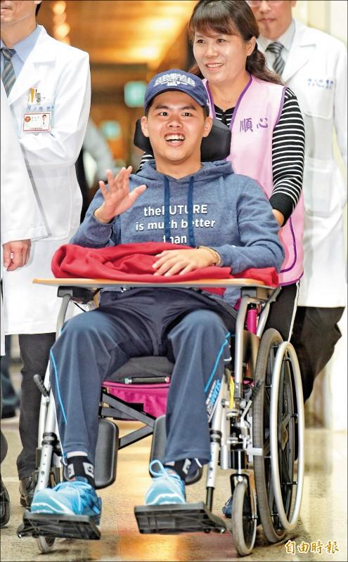 陸軍航特部下士秦良丰昨日揮手面露笑容,由台北三總轉院回高雄進行後續復健。(記者張嘉明攝)