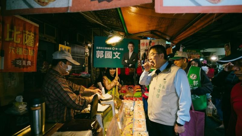 台南市長黃偉哲到新化市場幫忙立委補選候選人郭國文跑拜票行程,不忘買小點心吃,拉票兼拚庶民經濟。(記者洪瑞琴翻攝)