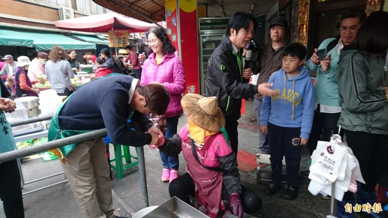 賴清德帶郭國文在西港菜市場拜票,郭國文彎腰九十度拉票。(記者楊金城攝)