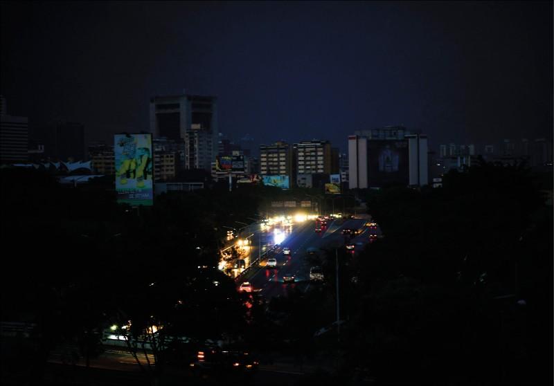 委內瑞拉七日起發生史上最嚴重的停電,幾乎癱瘓整個國家,圖為除了車燈外,首都卡拉卡斯八日晚間一片黑暗。(法新社)