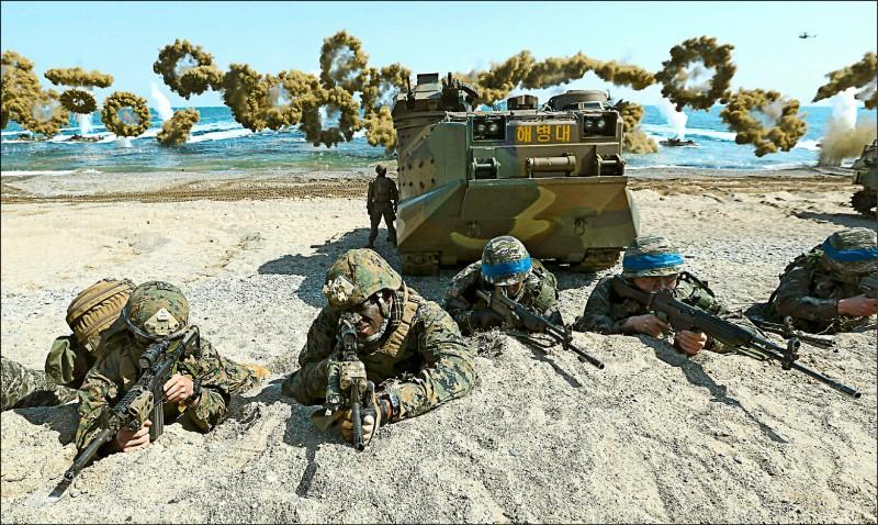 美軍陸戰隊員(左1、2)與鋼盔綁著藍色頭飾帶的南韓陸戰隊員,2016年3月在南韓慶尚北道浦項港海灘上舉槍瞄準,進行代號「雙龍」的美、韓聯合兩棲演習。雙龍是兩國每年春季兩項大規模聯合演習「關鍵決斷(Key Resolve)」及「鷂鷹(Foal Eagle)」的一環。(美聯社檔案照)