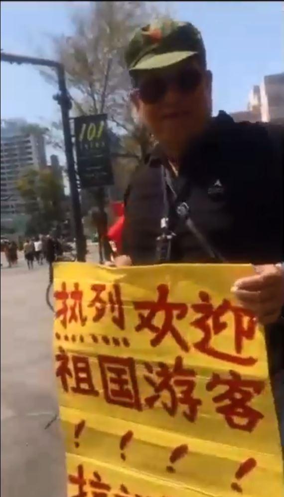 影片內涉嫌推人的中年男子頭戴中共軍帽,手拿「熱烈歡迎祖國遊客、抗議邪教騷擾遊客」的簡體字標語,自稱「也是台灣同胞」。(圖擷取自臉書粉絲專頁《臺灣爆報》)