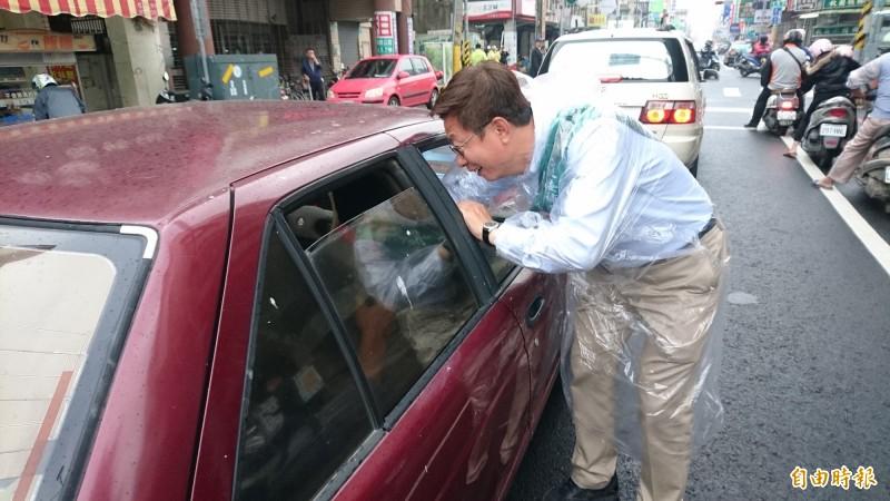 郭國文站麻豆街頭向鄉親問候拜票,連坐車內也要去握手。(記者楊金城攝)