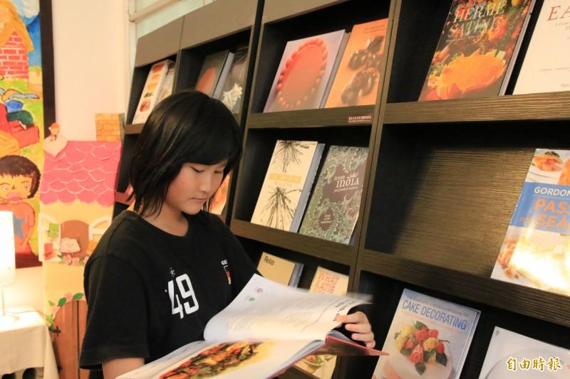 小朋友聚精會神閱讀王品集團暨益品書屋創辦人戴勝益推薦的餐飲書。(記者鄭名翔攝)