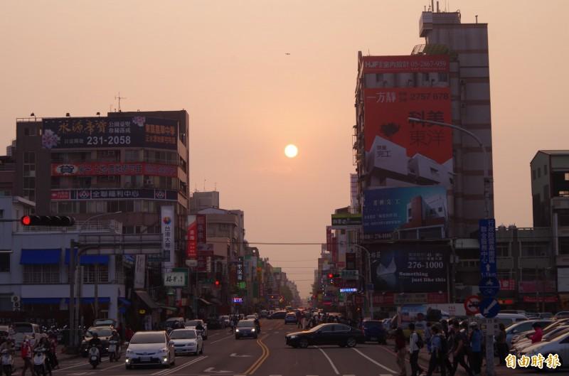 嘉義市民族路今天傍晚5點半左右,可見落日高掛,逐漸往民族路底移動,但因雲層過厚,約40分就看不到落日。(記者王善嬿攝)