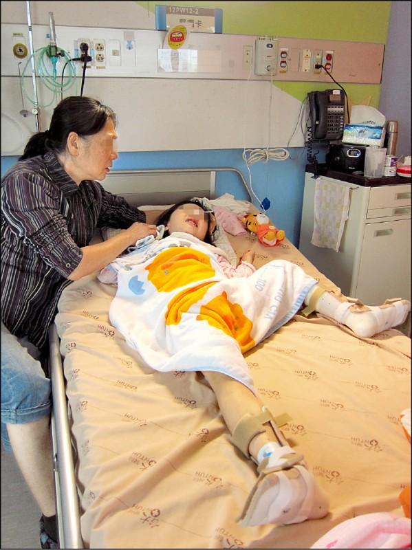 女童遭電擊後躺在病床上,四肢會不自主用力,為免關節受損扭曲,必須固定,阿嬤在一旁,紅了眼眶心疼的說「要減壽,保她周全」。(資料照)