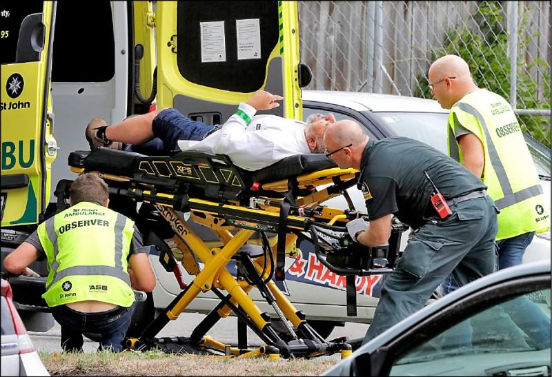 一名傷者被救護人員抬出遭攻擊的清真寺。(美聯社)