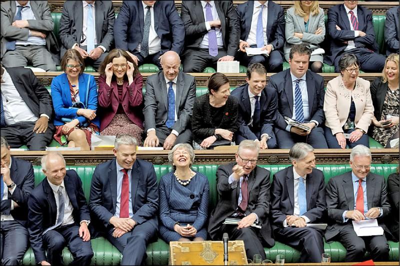 英國國會下議院當地時間十四日表決通過延後脫歐,但否決舉行第二次脫歐公投。這使英國首相梅伊(下排右四)又有機會推動下院同意她與歐盟達成的脫歐協議草案,也讓她在議場露出難得的笑容。 (路透)