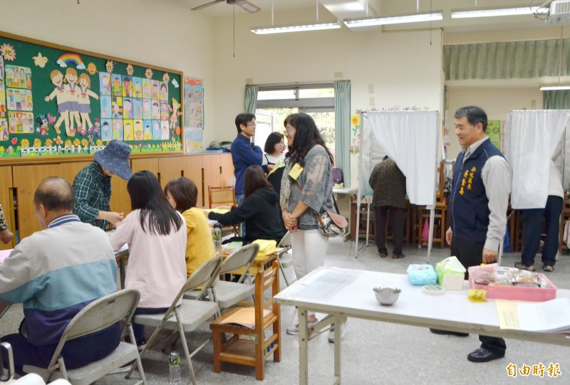 新化區長吳金喜(右1)視察投開票所,瞭解作業流程是否順利,並為選務人員打氣。(記者吳俊鋒攝)