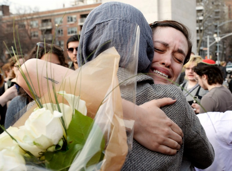紐國恐攻釀49死,民眾紛紛上街獻花為死者祈福,場面令人鼻酸。(路透)