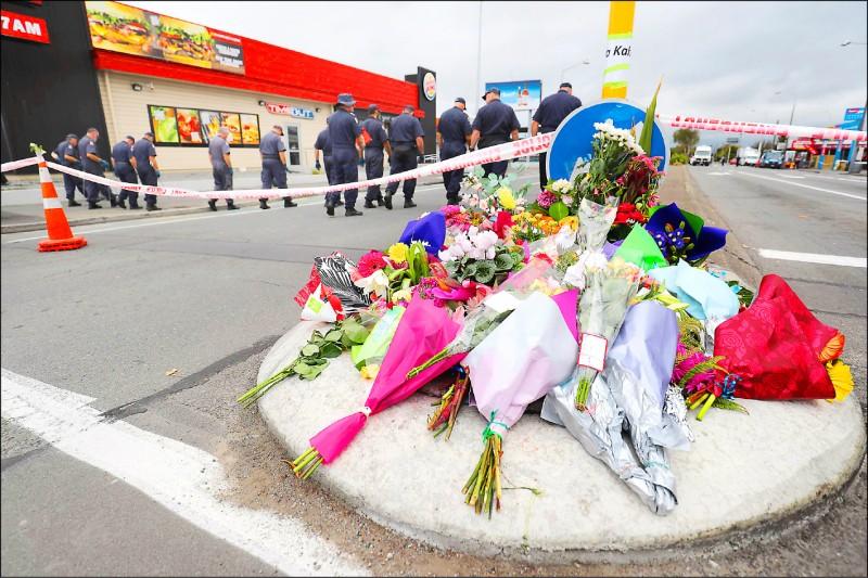 民眾16日在林伍德清真寺附近擺上花束與紙條,警方則持續在該區進行搜索。(法新社)
