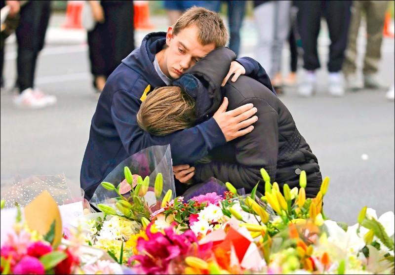 紐西蘭民眾16日在基督城努爾清真寺附近的臨時紀念處,悼念罹難者。(美聯社)