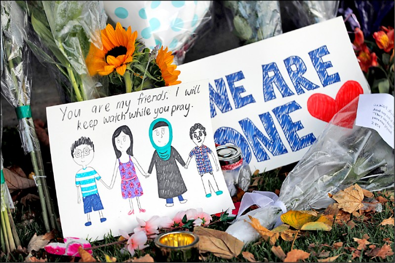 紐西蘭基督城植物園十六日堆滿花束與卡片,悼念植物園旁的努爾清真寺大屠殺罹難者。(美聯社)