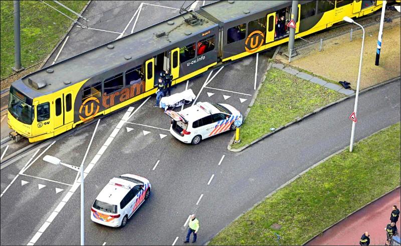 荷蘭十八日驚傳槍手在輕軌電車上開槍,地上可見一具覆蓋白色毯子的屍體。現場已被封鎖。(法新社)