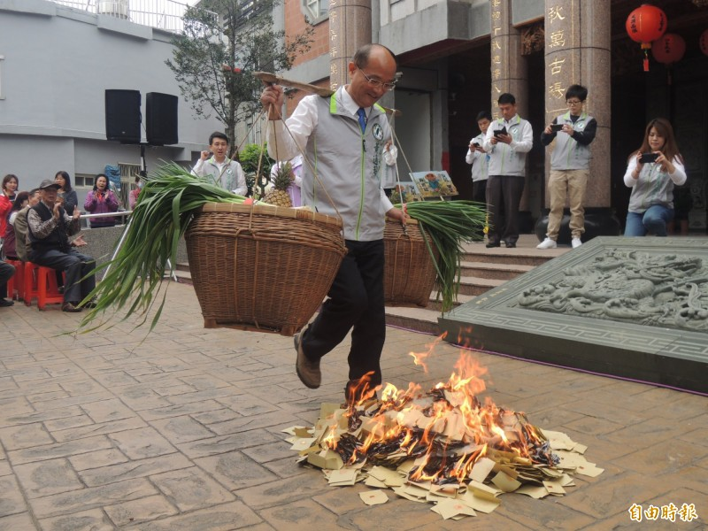 前宜蘭縣副縣長黃適超,今天宣布參選立委,他挑起擔子跨越金紙火堆,宣誓參選決心。(記者江志雄攝)