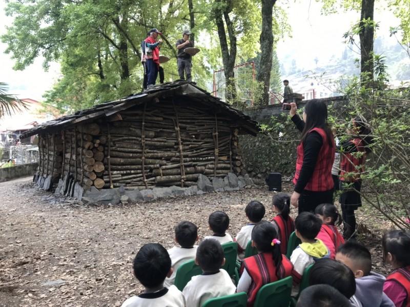 部落耆老站上傳統石板屋屋頂祈福,讓學童見識傳統習俗。(都達國小提供)