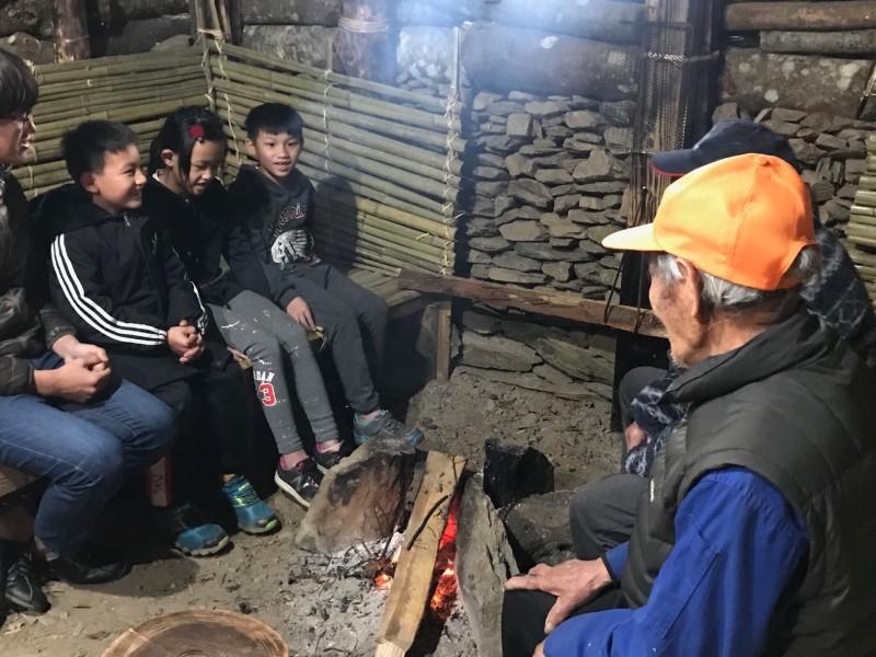 傳統石板家屋內升起火堆,學童圍坐,仔細聆聽部落耆老說故事。(都達國小提供)