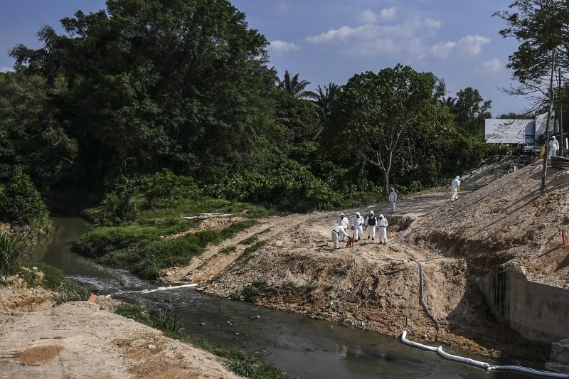 馬來西亞工業城市巴西古當(Pasir Gudang)的河流遭傾倒劇毒廢棄物,導致當地超過2700人病倒。圖為大馬官員在現場採集樣本。(歐新社)
