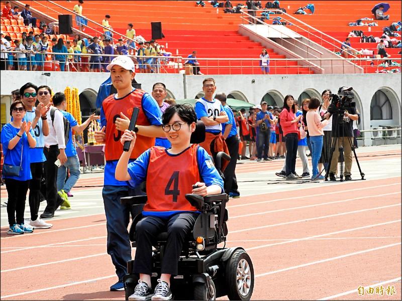 新北市府罹患肌肉萎縮症的員工陳彥瑀首次參加大隊接力賽,以輪椅滑行的方式「跑」完一百公尺。(記者賴筱桐攝)