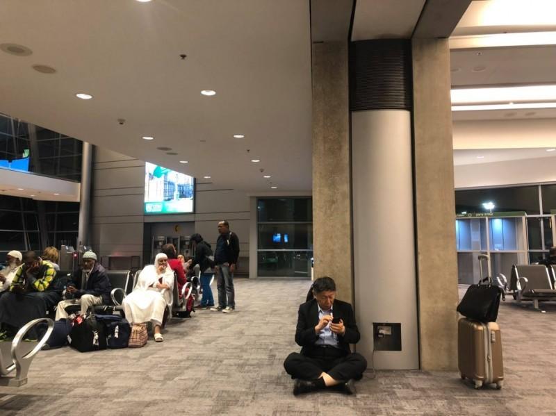 柯文哲上次訪美在機場席地而坐,邊滑手機邊充電,照片曝光引發爭議。(圖擷取自柯文哲臉書粉專)