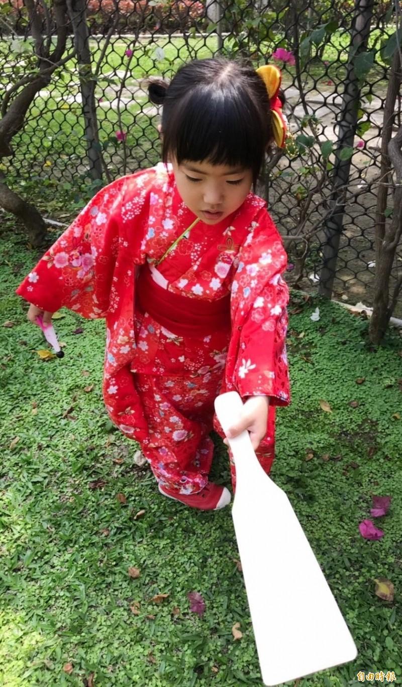 小朋友穿和服,體驗日本卡通哆啦a夢大雄、靜香過年時玩耍的板羽球遊戲。(記者蘇福男攝)