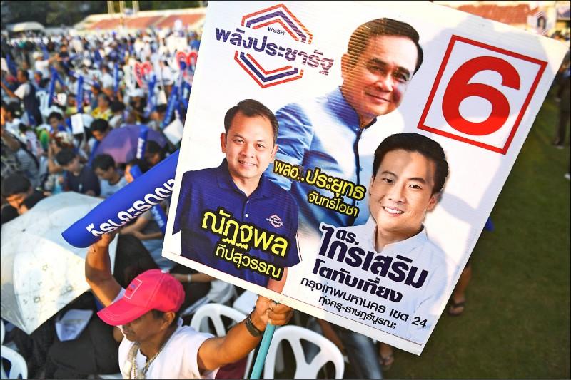 泰國「公民力量黨」支持者在二十二日的造勢晚會上,高舉現任軍政府總理帕拉育(中)等候選人海報,助長選舉氣勢。(法新社)