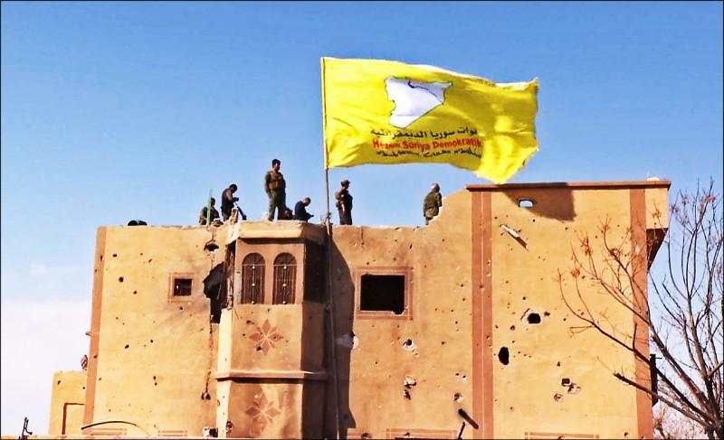 庫德族電視頻道廿三日公布的影像顯示,該族領導的「敘利亞民主力量」在攻克「伊斯蘭國」最後據點巴古斯村後,升起代表「敘利亞民主力量」的旗幟。(法新社)
