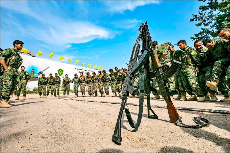 在敘國東部代爾祖爾省歐瑪油田附近的「敘利亞民主力量」戰士,聽到「伊斯蘭國」已被完全消滅後,載歌載舞慶祝。(法新社)