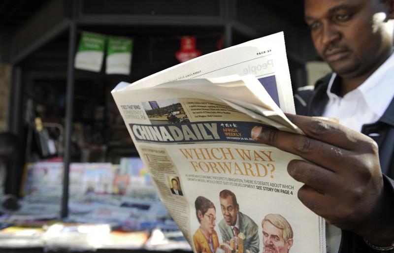 中國大力開發能觸及國際閱聽眾的媒體,透過不同語言「說好中國故事」,圖為一名讀者正在閱讀非洲版《中國日報》。(法新社)