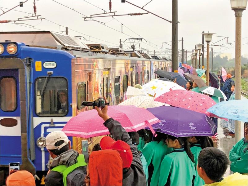 台鐵首度與拱天宮合作,打造白沙屯媽祖彩繪列車,昨日首發停靠白沙屯站,吸引許多信徒爭相拍照。(中央社)