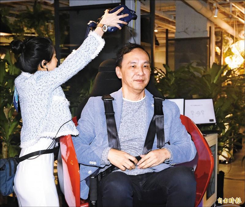 對於初選爭議,前新北市長朱立倫昨籲黨中央或黨主席吳敦義能夠面對面和高雄市長韓國瑜談。圖為朱昨體驗VR遊戲時,工作人員為他戴上頭盔。(記者廖振輝攝)