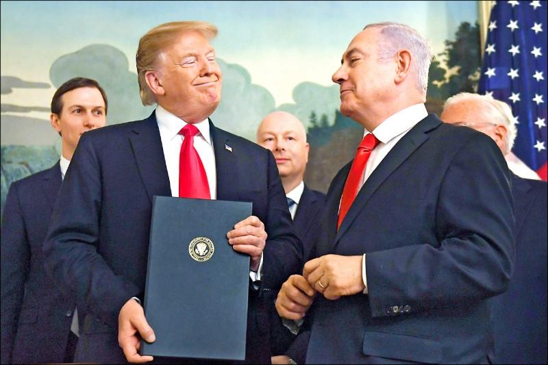 美國總統川普(左)廿五日簽署總統文告,「承認戈蘭高地乃以色列的一部分」,隨後捧著它對來訪的以色列總理納坦雅胡(右)報以微笑。(美聯社)