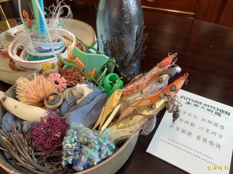 宛如海鮮大拼盤的海漂垃圾創作,一旁擺有「海洋直送、新鮮擺盤」標語,用詼諧、暗諷手法表現警示意味。(記者王峻祺攝)