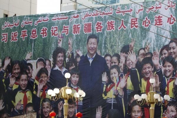 新疆維吾爾族遭受中國當局迫害,當地掛著習近平海報。(美聯社)